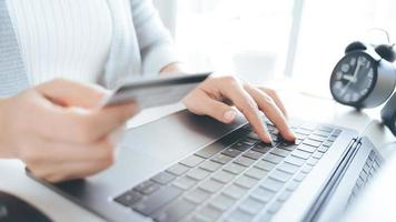 Woman hand holding credit card and using laptop. Online payment, Online shopping concept photo