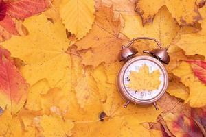 otoño hojas de otoño y despertador. tiempo de otoño creativo plano laico foto