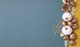 Minimalistic autumn Banner with copy space and golden acorns, cones, leaves and pumpkins on an colorful background. photo