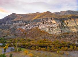 Aerial perspective of Vardzia-cave city from above with paravani river and autumn nature in foreground. Historical unesco sites Georgia. photo
