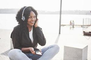 Portrait of a beautiful young pretty African American girl sitting on the beach or lake and listening to music in her headphones photo