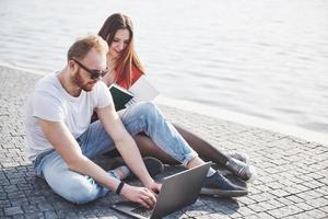 Dos estudiantes, chico y chica, están sentados al aire libre y disfrutando de una computadora portátil, estudiando al aire libre en un día soleado foto
