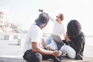 Hermosos amigos multiétnicos usando una computadora portátil en la calle y hacen selphie. concepto de estilo de vida juvenil foto