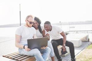 hermosos amigos multiétnicos usando una computadora portátil en la calle. concepto de estilo de vida juvenil foto