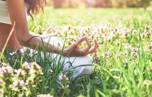 La meditación del yoga en un parque sobre el césped es una mujer sana en reposo foto