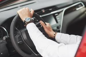 A businessman rides his car, moves on the wheel. A watch on hand in a man's divorce. photo