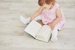 Beautiful little girl read book with her favorite bear on a soft plush blanket photo