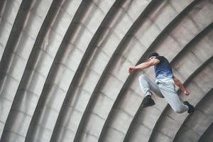 young man doing parkour jump in urban space in the city sunny spring summer day. photo