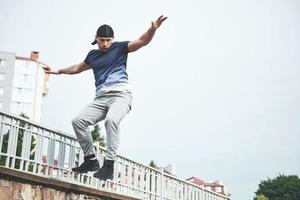Young sports man doing parkour in the city. photo