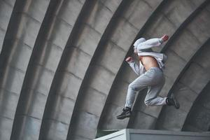 A young man is jumping. Parkour in urban space, sporting activity. photo