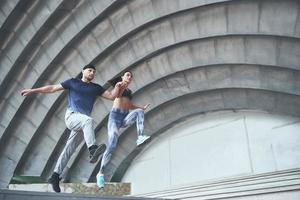 Young happy sports couple in the city street, performing parkour. photo