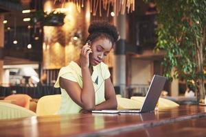 Young beautiful African-American business woman talking on the phone while working in a cafe photo