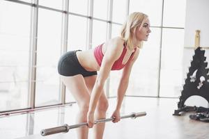 Woman lifting weights in gym Concept workout healthy lifestyle sport photo