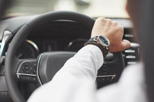 A businessman rides his car, moves on the wheel. Hand with watch photo