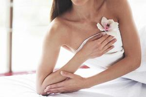 Beautiful body woman with white flower orchid and body care. photo
