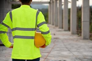 A worker in the uniform holding helmet for safety in the working construction site photo
