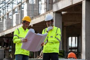 Supervisors engineering reading blueprint at construction site photo