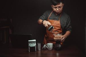 barista haciendo goteo de café y la felicidad del joven en la cafetería del café foto