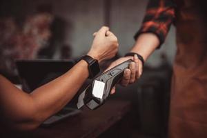 Pago SmartWatch con lector de tarjetas de crédito en el café de la máquina foto