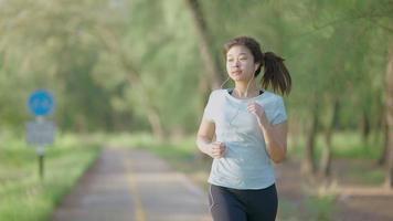 Asian girl jogging by the garden video