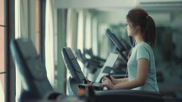 Young woman walking on the treadmill and listening to music at the gym video