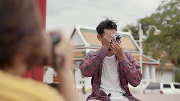 Touristen asiatischer Mann mit Filmkamera, der ein Foto macht, während er auf der Straße in Thailand sitzt. video
