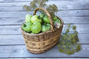Basket with vegetables and herbs. Tomatoes and dill in a wicker basket on a wooden background. photo