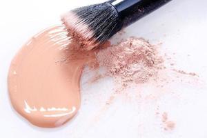 Base de maquillaje beige líquido manchado sobre fondo blanco. foto