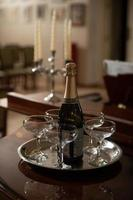 A tray with glasses of champagne and a bottle of sparkling wine. photo