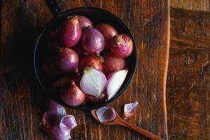 Cebollas rojas frescas en la sartén sobre la mesa de la cocina foto