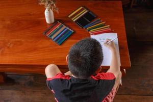 un niño sentado en su casa dibujando y pintando. foto