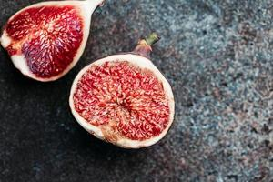 Macro photography of fresh ripe cutted figs on the textured background. photo