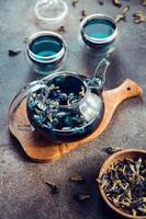 Thai Butterfly pea tea in a glass teapot and cups on a table. photo