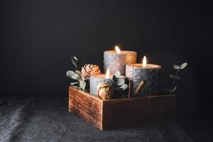 New Year festive decorations with wooden box and black burning candles in a dark interior. photo
