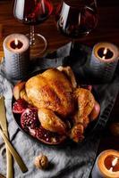 pollo entero asado con granada, manzana y vino tinto en una mesa festiva. foto