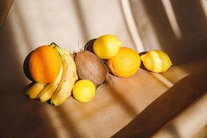 Creative summer food still life with bananas, coconut, oranges and lemons. photo
