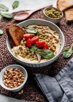 hummus con guisantes, piñones, tomates y acelgas. plato vegetariano saludable, vista superior. foto