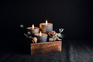 Decorations with wooden box and black burning candles in a dark interior. photo
