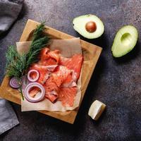 ingredientes para hacer un sándwich saludable. bollo de pan de centeno, salmón, aguacate, cebolla, eneldo y limón. vista superior. foto
