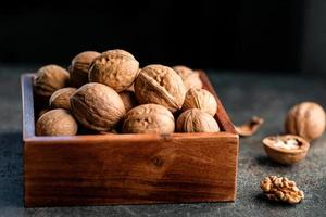 Close-up of walnuts in a shell in a wooden box on a table. photo
