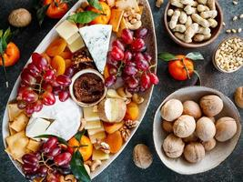 Big cheese board with appetizer assortment. Grape, cheese, nuts, jam and bread. photo