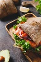 Healthy sandwich with rye bread bun, salmon, avocado, onion and salad served on a wooden rustic board. photo