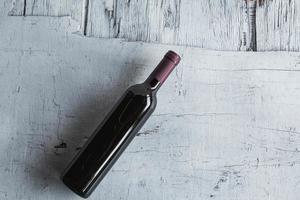 Botellas de vino sobre fondo de madera blanca foto