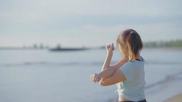 Teenage girl stretching by the beach video