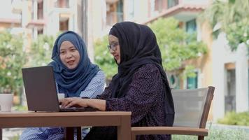 Two good-looking Muslim women working outside the slogan work form home video