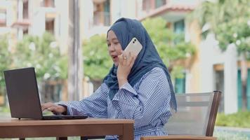 good looking Muslim women sitting outside working according to the slogan work form home video