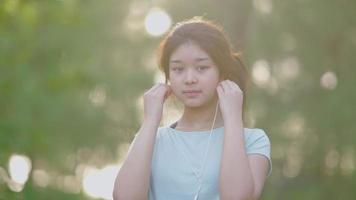 Asian cute girl She was wearing headphones listening to music and smiling video