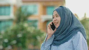 asian muslim woman standing and talking on the cell phone video