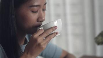 Asian woman drinking coffee and working. video