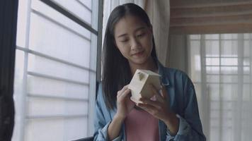 Young Asian woman freelance architect holding model of home standing beside window at home office. video